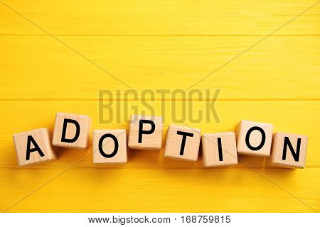 Cubes with word ADOPTION on color wooden background