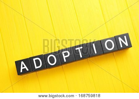 Black cubes with word ADOPTION on color wooden background