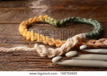 A low angle image of a crochet heart and three crochet hooks.