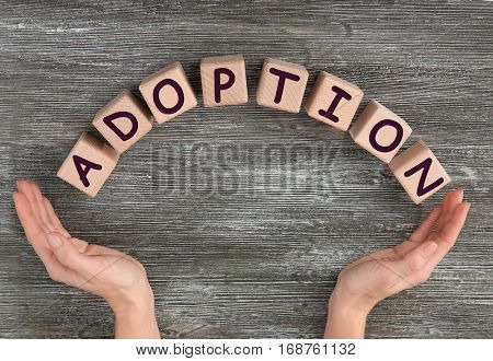 Female hands and cubes with word ADOPTION on wooden background