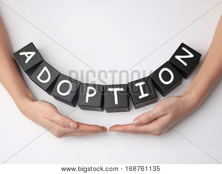 Female hands and black cubes with word ADOPTION on white background