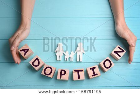 Female hands, cubes with word ADOPTION and figure in shape of happy family on wooden background