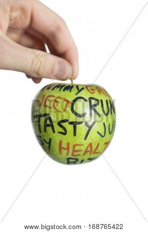 Cropped image of hand holding a granny smith apple with orthographic text over white background