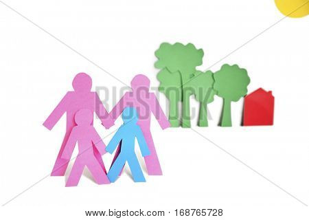 Paper cut outs representing a family with trees and house over white background