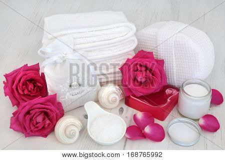 Pink rose flowers with spa beauty treatment cleansing products on white distressed wood background.