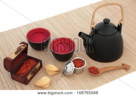 Safflower tea with oriental teapot, cups,fortune cookies, strainer, old wooden spoon and caddy box on bamboo over white background. Used also in chinese herbal medicine.
