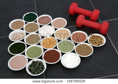 Body building powders and vitamin pill supplements with dumbbell weights over slate background.