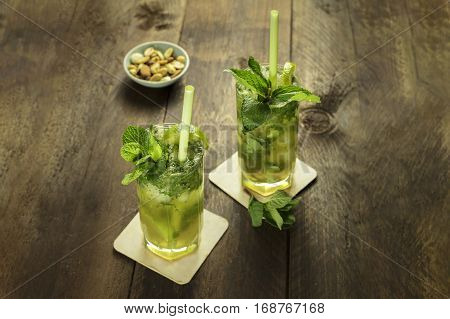 A photo of mojito cocktails with mint leaves, wedges of lime, drinking straws, and a snack, on a dark wooden background with copy space. Selective focus