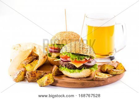 homemade burgers with beef and fried potatoes and glass of cold beer on white background