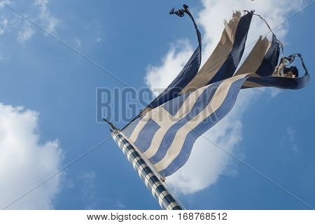 Worn out Greek national flag with cloudy sky background
