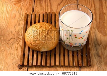 Bun with sesame seeds and a transparent glass of milk on wooden background