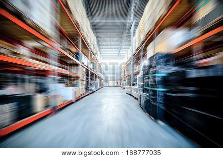 Warehouse industrial and logistics companies. Commercial warehouse. Boxes and crates stocked on the shelves of three storey. Motion blur effect.