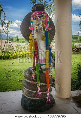 Thailand Krabi Town. The open gazebo-Temple (sala) snake goddess Manasa responsible for fertility so the snakes honored women who wish to have many children. Statuette of the sacred cobra.