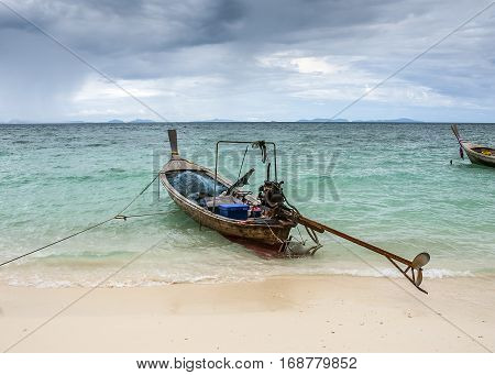 Thailand Krabi Province. Fishing village on one of the many islands in the sea. Fishing boats longtail moored on the beach.