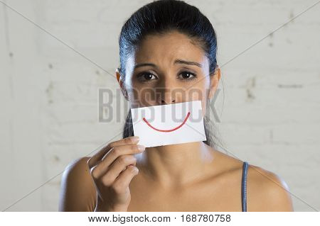 young beautiful sad and depressed woman hiding her true sorrow and sadness behind a paper with a drawn smile in conceptual fight the depression concept isolated on clear background