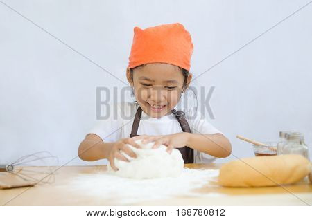 Close up shot of Asian little girl kneading the dough for making the bakery on white background