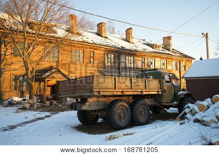 NAZIYA, RUSSIA - JANUARY 21, 2017: The old Soviet truck ZIL-157 at the abandoned wooden house in beams setting the sun