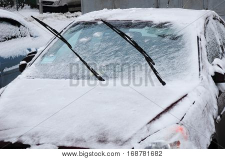 Car covered with fresh white snow in early winter