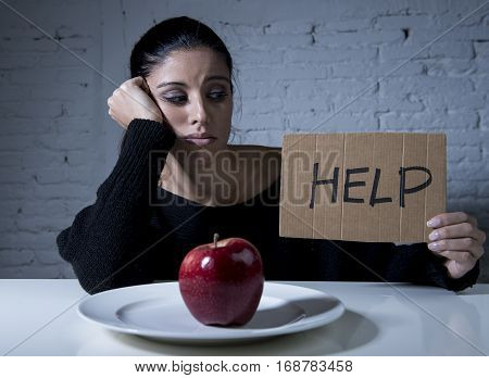 young woman or teen looking apple fruit on dish as symbol of crazy diet in nutrition disorder concept anorexia and bulimia and refusing to eat food in diet calories obsession asking for help