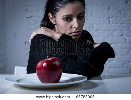 young woman or teen looking apple fruit on dish as symbol of crazy diet in nutrition disorder concept anorexia and bulimia and refusing to eat food in diet calories obsession