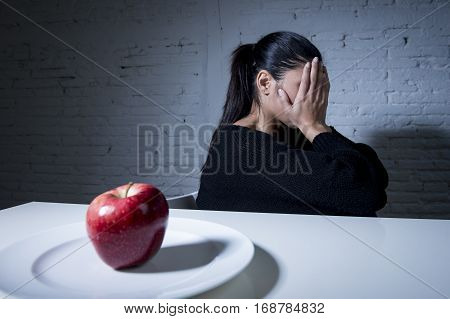 young woman or teen and apple fruit on dish as symbol of crazy diet in nutrition disorder concept anorexia and bulimia and refusing to eat food in diet calories obsession