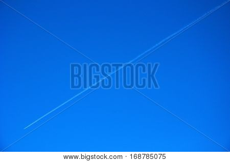 Airplane in Blue Sky with Condensation Trail. Vapour trails