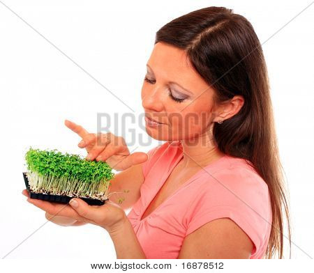 Portrait of a beautiful happy young woman holding green plants. ( Garden cress )
