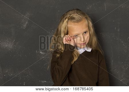 7 or 8 years old little beautiful blond schoolgirl crying sad moody and tired in front of school class blackboard in child school education concept isolated on white background