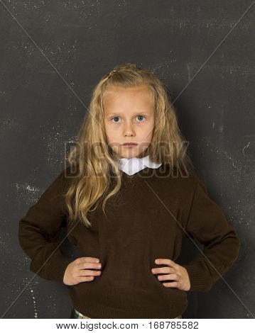 7 or 8 years old little beautiful blond schoolgirl sad moody and tired in front of school class blackboard in child school education concept isolated on white background