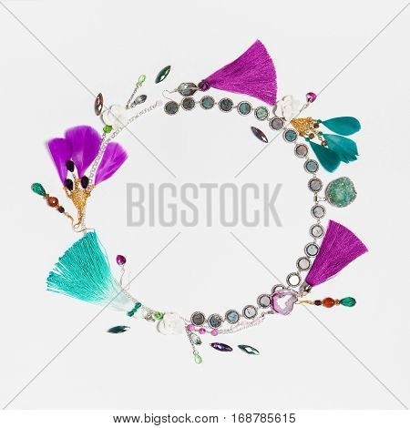 Handmade turquoise and violet bijouterie circle garland with earrings, necklace, gems, tassels and feathers in boho style, lying flat on the white square background, top view