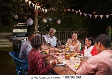 Adult black family enjoying dinner together in their garden