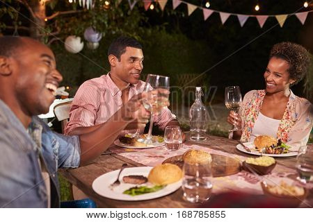 Three young black adults enjoying a garden dinner party