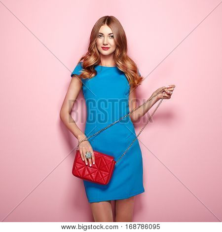 Blonde young woman in elegant blue dress. Girl posing on a pink background. Jewelry and hairstyle. Girl with red handbag. Fashion photo
