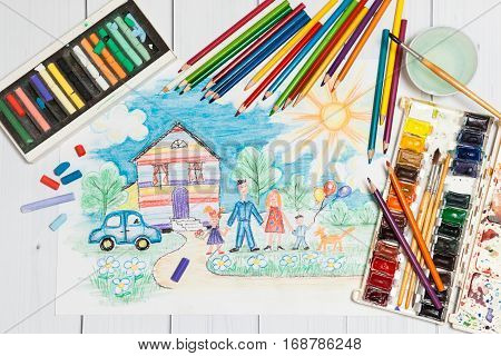 Hand drawn Bright Childrens Sketch With Happy Family, House, Dog, Car on the Lawn with Flowers with lying flat pencils, paints and pastel - concept of children creativity, close up top view