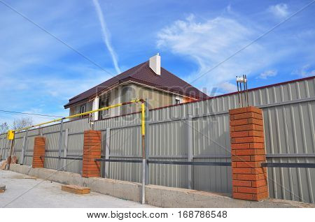 Building a Metal and Concrete Bricks Fence with Iron Bar Framework Natural Gas Pipeline.