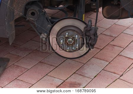 Disk brake on a car here Mechanic at the car brake repair in a car service workshop