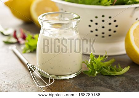 Homemade lemon ranch dressing in a small jar with fresh greens