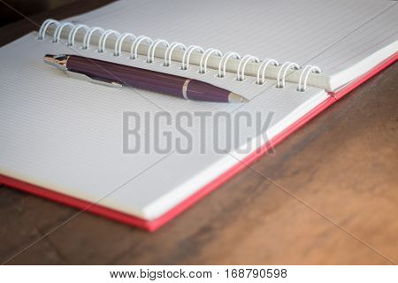 Pen and noteboook paper on wooden table stock photo