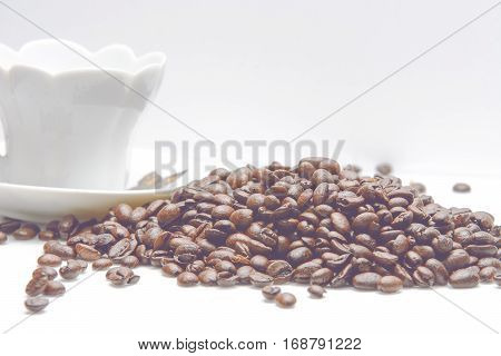 Coup of coffe alongside with coffe beans on white background