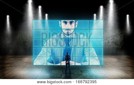 Young businessman looking at a big screen and talking to hologram.