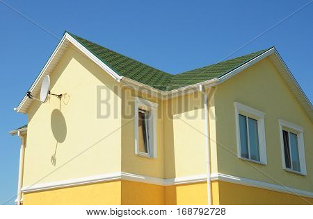 Colorful house facade walls with rain gutter downspout and green roof