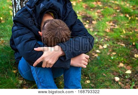 Sad Teenager sit on the Grass in the Park