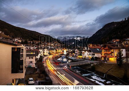 Val Gardena, Italy. Evening on the popular winter resort Ortisei of Val Gardena, Italy. Dolomites alps mountains at sunset. Illuminated hotels, cafes and restaurants, car traffic lights