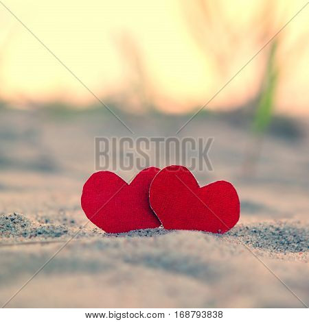 Toned Photo of Two Red Hearts in the Sand at the Evening Beach