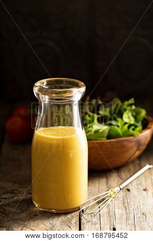 Homemade honey mustard salad dressing in glass bottle