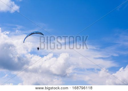 man on a parachute flying in the clear sky, a lovely summer day