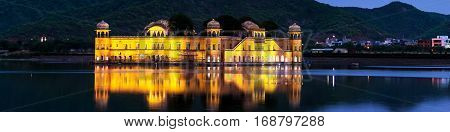 Illuminated Jal Mahal palace at night in Jaipur India. Popular landmark surrounded by water. Mountains at the background in Jaipur India
