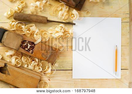 White sheet on wooden table for carpenter tools with sawdust. Copy space. Top view.