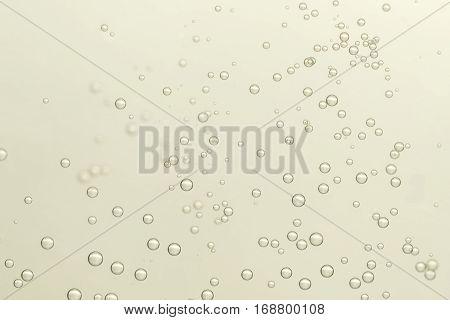 Golden champagne fizz bubbles soars over a golden background