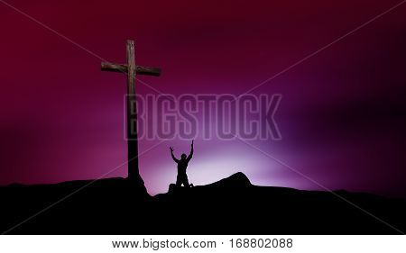 Silhouette of man praying before a cross at sunset concept of religion